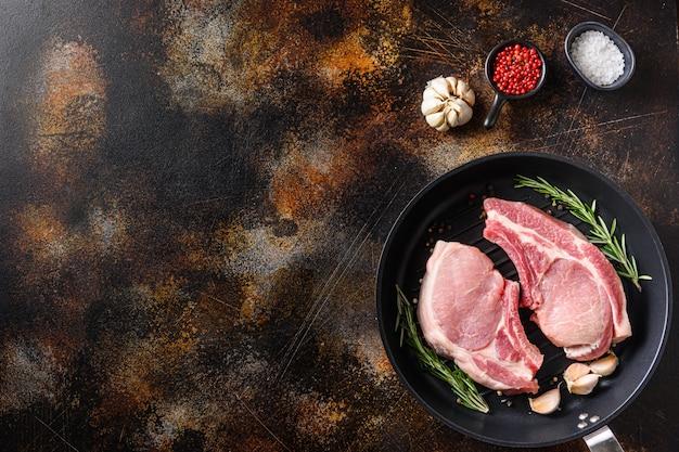 Мясо свинины, котлета на черной сковороде-гриле на старой деревенской темной металлической поверхности Premium Фотографии