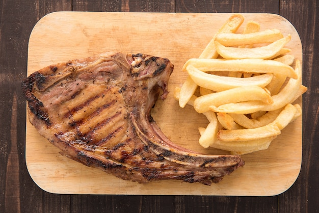 Pork meat grilled and french fries on wooden table. Premium Photo