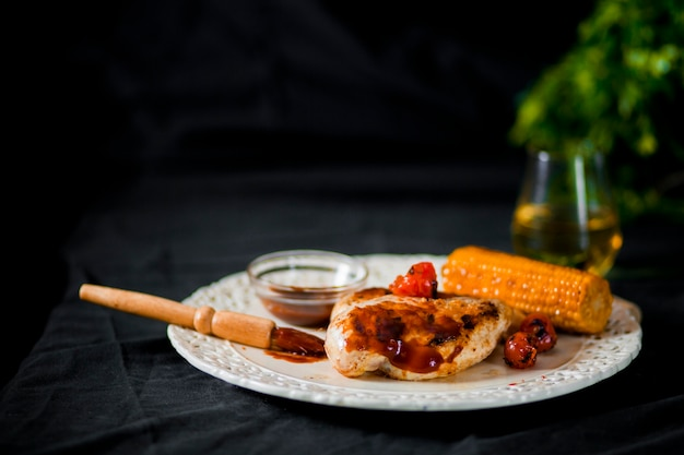 Pork meat with cherry tomato and corn on plate Free Photo