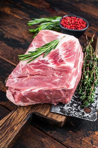 Сырое мясо свиной шеи для свежих стейков на деревянной разделочной доске с ножом для мясника. темное дерево Premium Фотографии