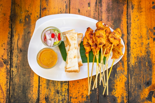 Pork satay with coconut milk and bread  with sauce in white plastic plate on wooden table. Premium Photo