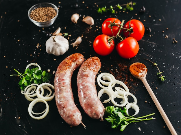 Pork sausage for marinade and other spices: tomatoes, parsley, garlic, and others on a black background Premium Photo