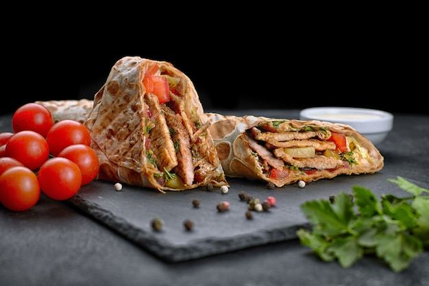 Pork shawarma, on a black background, with herbs, tomatoes and sauce Premium Photo