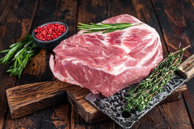 Сырое мясо из свиной лопатки для свежих стейков на деревянной разделочной доске с ножом для мясника. темное дерево Premium Фотографии