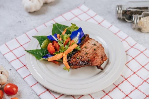 Bistecca di maiale con pomodoro, carota, cipolla rossa, menta piperita, fiore di pisello farfalla e lime. Foto Gratuite