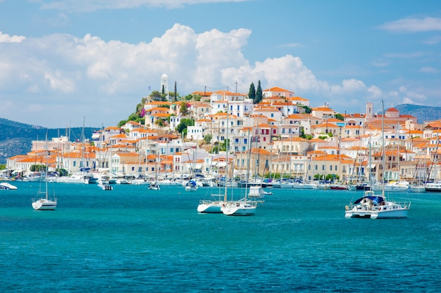 Poros, greece - june 08, 2016: a beautiful view of the wonderful port city on the sky background in greece Premium Photo