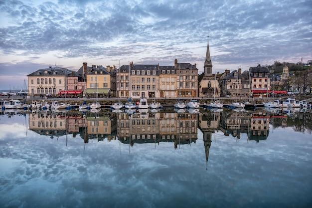 프랑스의 흐린 하늘 아래 물에 반영된 건물이있는 옹플 뢰르 항구 무료 사진