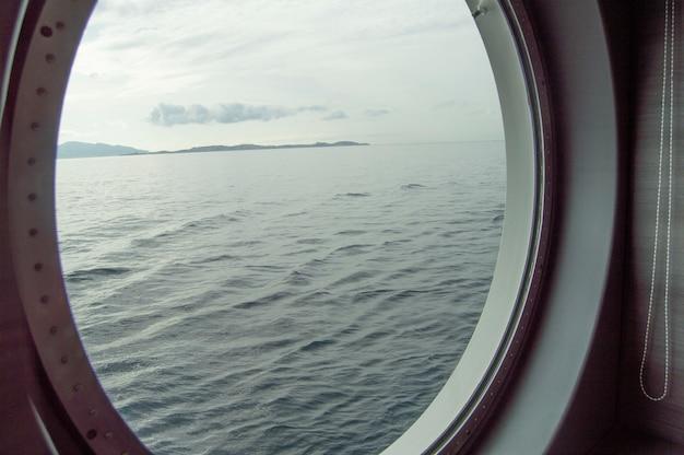 クルーズ船の丸いport窓、海岸と海の窓からの内部ビュー、海に対する日の出、クローズアップ Premium写真