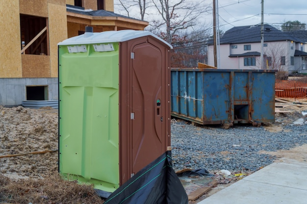 Portable restroom on a dumpsters being full with garbage new house under construction. Premium Photo