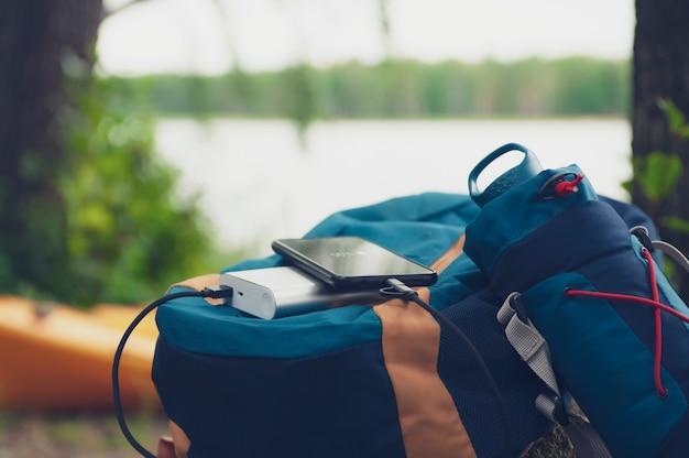 ポータブル旅行充電器。パワーバンクは、旅のバッグ、湖、森を背景にスマートフォンに課金します。 Premium写真
