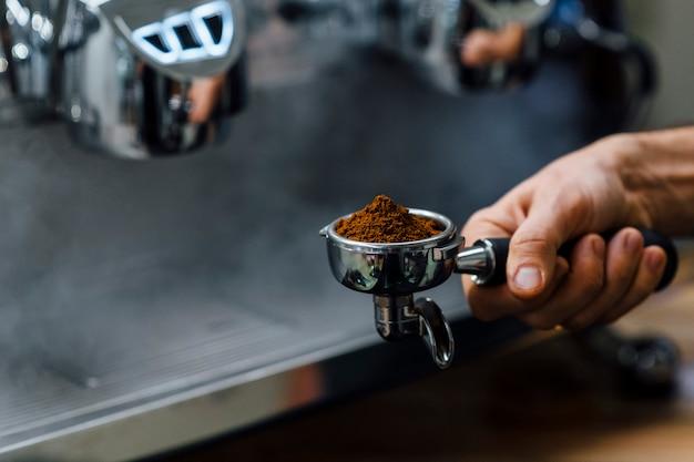 Деталь рука человека, держащего portafilter получателя заполнены кофейной гущи во время приготовления эспрессо Premium Фотографии