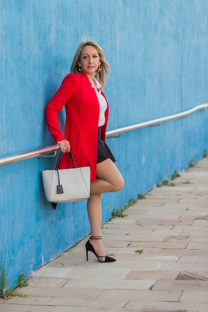 Portait of a blonde elegant woman wearing red jacket leaning on a metallic fence on a wall Premium Photo