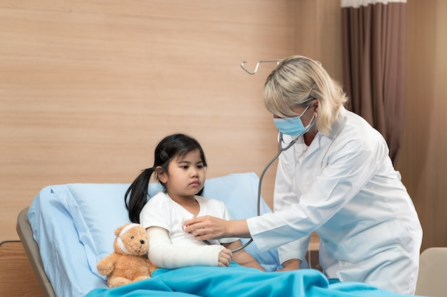 Portarit of smaile doctor pediatrician and little girl patient on bed with teddy bear Premium Photo