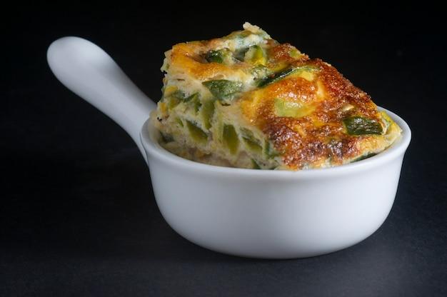白いセラミックボウルに野菜のオムレツの部分 Premium写真