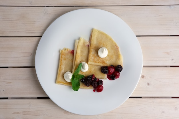 Portion on thin pancakes with sweet cream cheese and berries. top view. Premium Photo