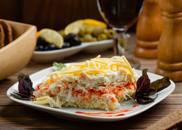 Portioned mimosa salad with egg white, steamed carrot, potato, cheess Free Photo