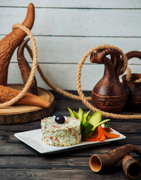 Portioned olivier salad garnished with cucumber and carrot flowers Free Photo