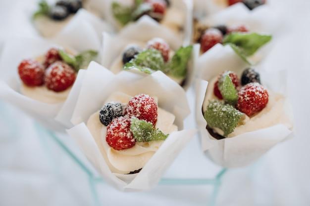 Porzioni di dessert decorate con panna e frutti di bosco Foto Gratuite