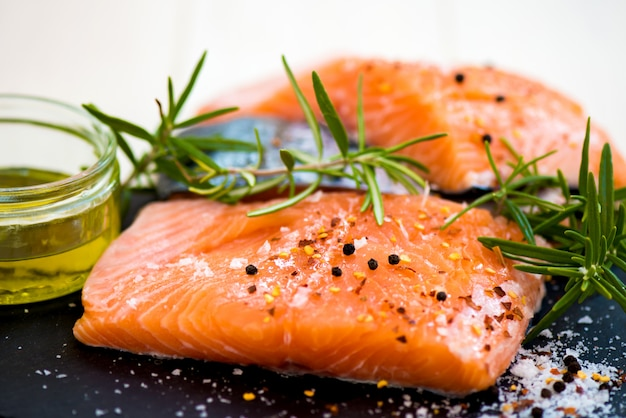 Portions of fresh raw salmon fillets with aromatic herbs and olive oil Premium Photo