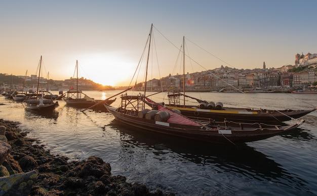 Городской пейзаж порту в закат с рекой на фронте и винный корабль на переднем плане и город порту в фоновом режиме, португалия Premium Фотографии