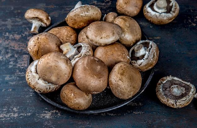 Portobello mushroom、ブラックプレート。暗い、トップビュー Premium写真