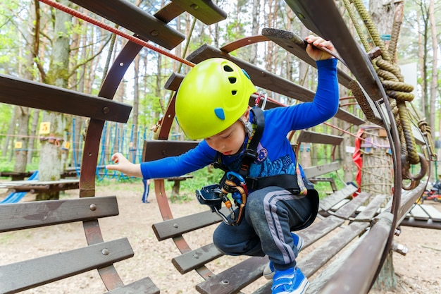 Portrait of 3 years old boy wearing helmet and climbing Premium Photo