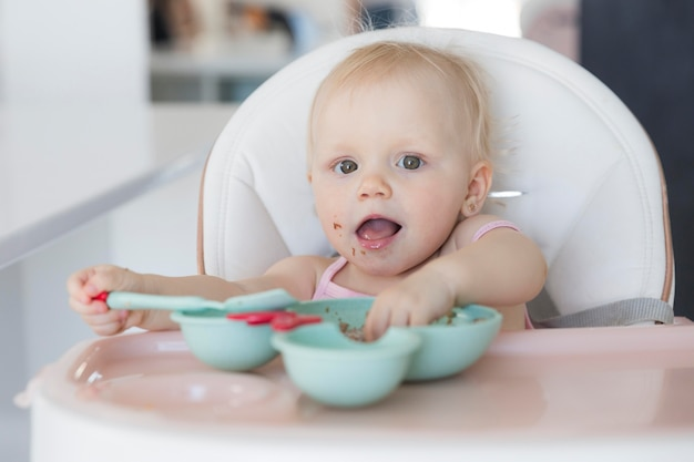 Portrait of adorable baby girl playing with food Free Photo