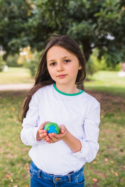 Portrait of a adorable girl holding clay planet world in park Free Photo