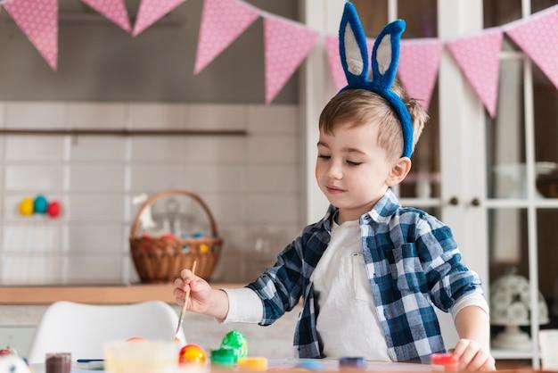 Portrait of adorable little boy painting eggs Free Photo