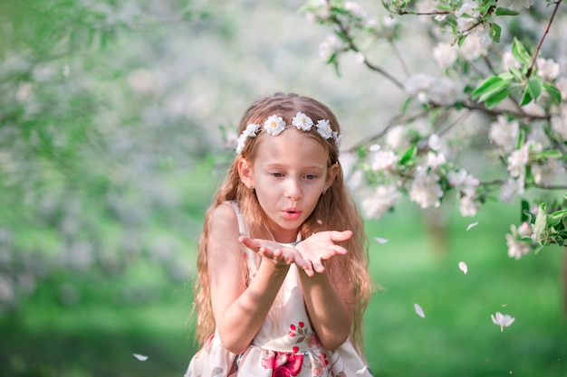 Portrait of adorable little girl in blooming cherry tree garden outdoors Premium Photo