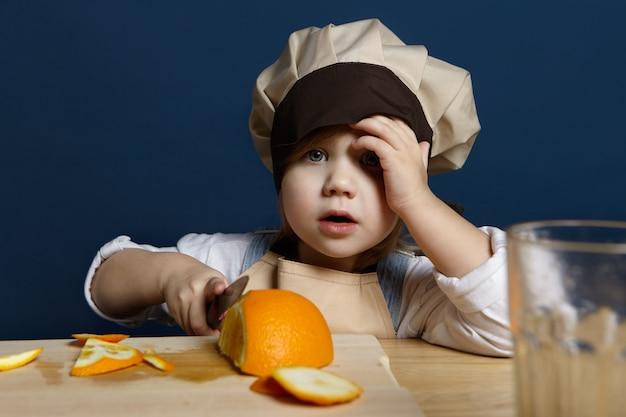 Ritratto di adorabile bambina in chef copricapo e grembiule taglio arance sul bordo di cottura utilizzando un coltello, rendendo il succo di agrumi fresco o una sana colazione. vitamina, freschezza, dieta e concetto di nutrizione Foto Gratuite