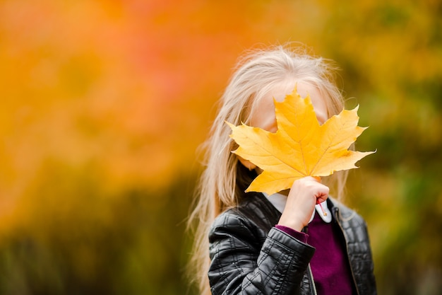 Portrait of adorable little girl with yellow leaves bouquet in fall on scooter Premium Photo