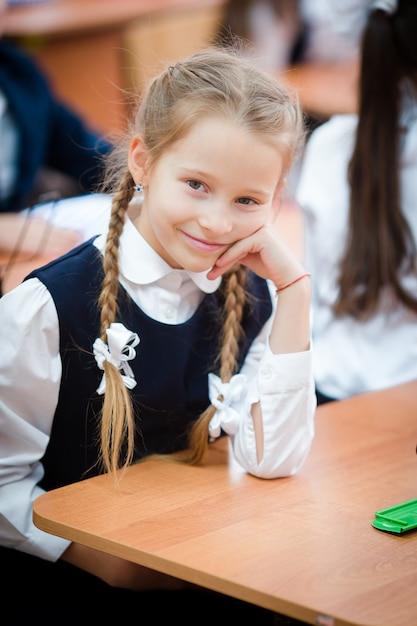 Portrait of adorable little school girl in classroom Premium Photo