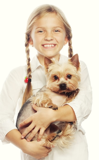 Portrait of an adorable young girl smiling holding a cute puppy Premium Photo