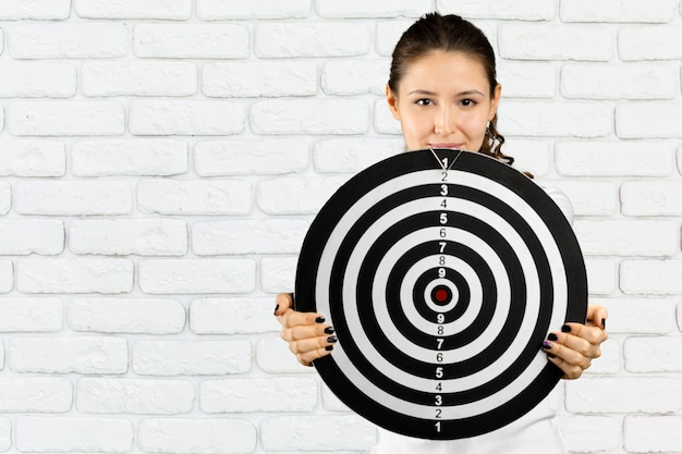 Portrait of adult blonde woman with board for darts Premium Photo