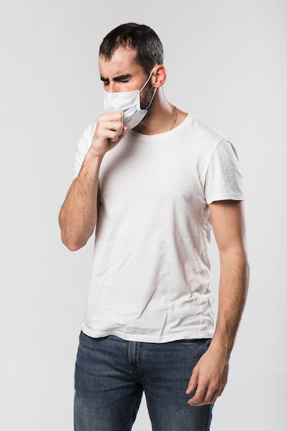 Portrait of adult male with face mask coughing Free Photo