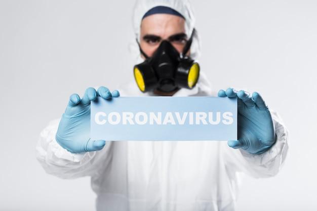 Portrait of adult with face mask holding coronavirus sign Free Photo