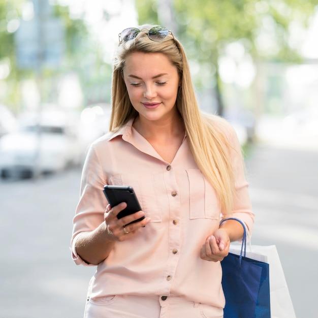Ritratto del telefono mobile di lettura rapida della donna adulta Foto Gratuite