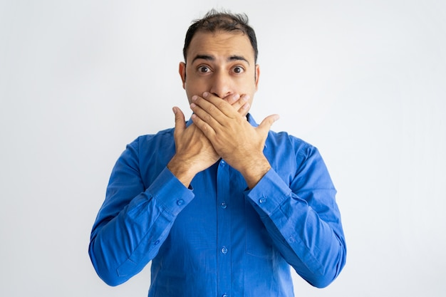 Portrait of afraid mid adult businessman covering mouth Free Photo