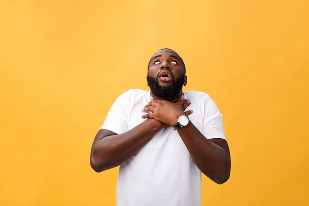 Portrait of african american man with hands raised in shock and disbelief. isolated over yellow background. Premium Photo