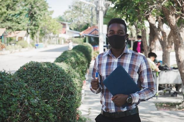 Portrait of african teacher in face mask standing outdoor at school Premium Photo