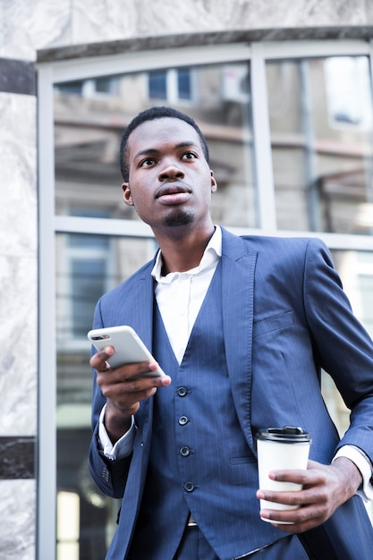 Ritratto di un giovane uomo d'affari africano in vestito blu che tiene tazza di caffè da asporto utilizzando il telefono cellulare Foto Gratuite
