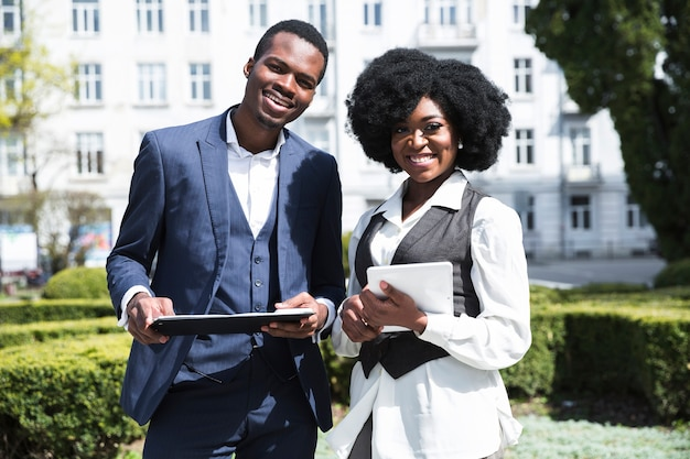 Portrait of an african young businessman and businesswoman holding clipboard and digital tablet looking at camera Free Photo