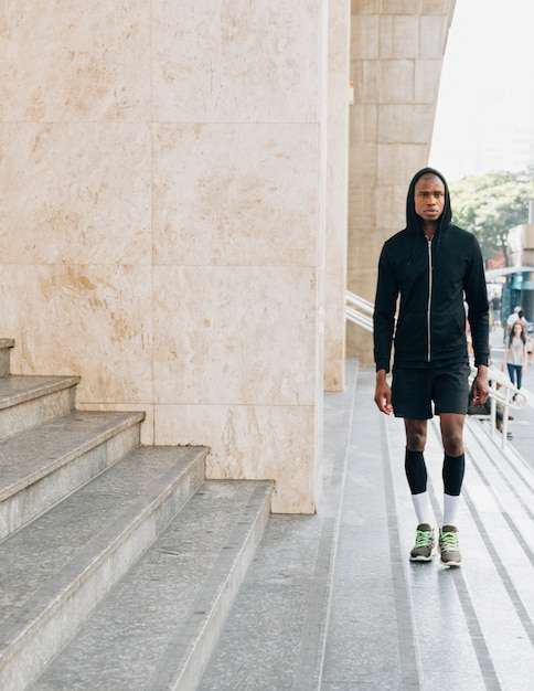 Portrait of a african young male athlete in black hoodie standing near the steps Free Photo