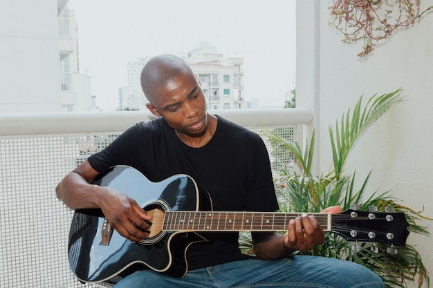 Portrait of an african young man sitting in the balcony playing guitar Free Photo