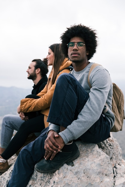 Portrait of an african young man sitting on mountain peak with his friends looking at camera Free Photo