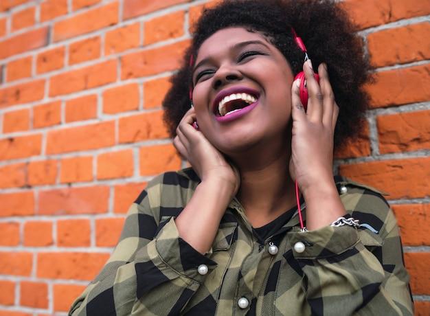 Ritratto di donna afroamericana latina sorridente e ascolto di musica con le cuffie contro il muro di mattoni. all'aperto. Foto Gratuite