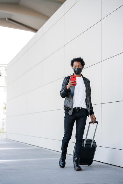 Ritratto di turista afro uomo utilizzando il suo telefono cellulare e portando la valigia mentre si cammina all'aperto Foto Gratuite