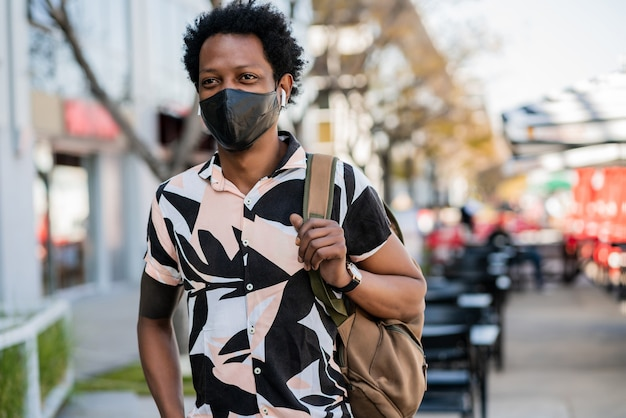 Portrait of afro tourist man wearing protective mask while standing outdoors on the street Free Photo