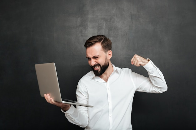 Portrait of agressive bearded man holding silver personal computer and throwing punch in screen, isolated over dark gray wall Free Photo